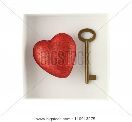 Red painted wooden heart and bronze key in white pared box isolated on white background