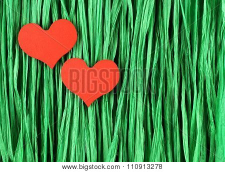 Two red painted wooden hearts on green paper raffia strips background