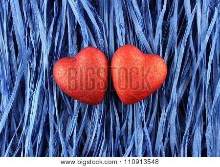 Two red painted polyfoam hearts on blue paper raffia strips background