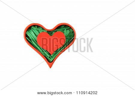 Red painted wooden heart enclosed with green paper raffia strips in red box isolated on white backgr