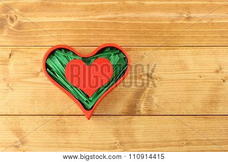 Red painted wooden heart enclosed with green paper raffia strips in red box on wooden background