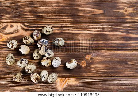 quail eggs on a brown wooden background.