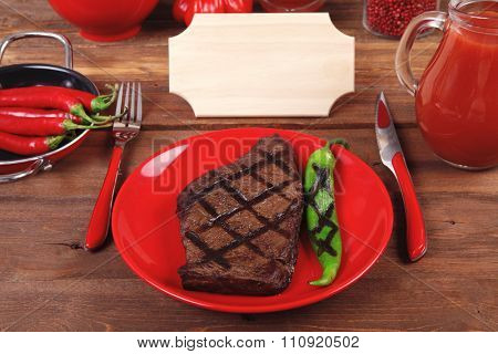 red theme lunch : grilled bbq roast beef steak red plate green chili tomato soup ketchup sauce paprika small glass ground pepper american peppercorn modern cutlery served wooden table empty nameplate