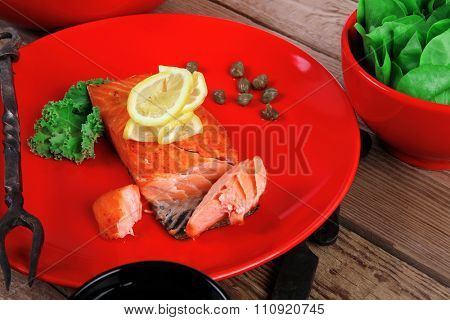 delicious portion of fresh roast salmon fillet on red plate with green salad kale tomato soup bbq sauce and black coffee over wooden table - healthy food, diet cooking concept kale tomato soup