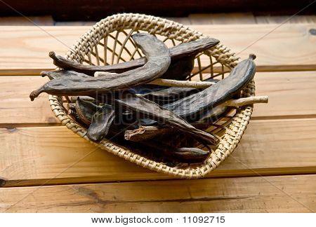 Dry Organic Carob Pods In A Straw Basket