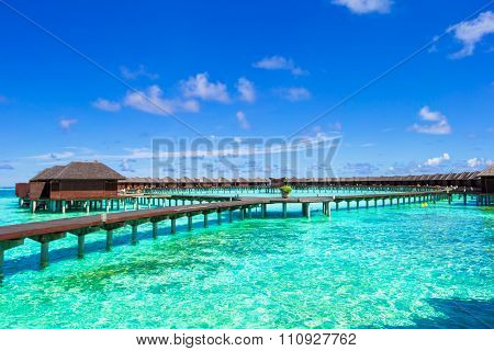 Water bungalows and wooden jetty on tropical island in Indian Ocean