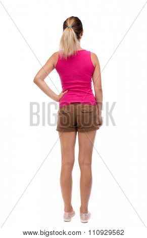 back view of standing young beautiful  woman.  girl  watching. Rear view people collection.  backside view of person.  Blonde girl in shorts and a pink blouse is resting his hand in his left side.