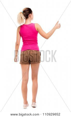 Back view of  woman thumbs up. Rear view people collection. backside view of person. Isolated over white background. Blonde girl in shorts and a pink blouse is showing the right hand thumb up.
