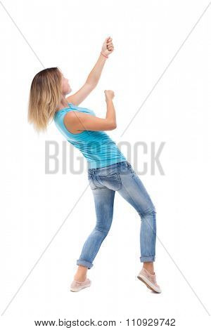 back view of standing girl pulling a rope from the top or cling to something. girl  watching. Isolated over white background. blonde in a blue shirt and jeans, he pulls top rope for turning right side