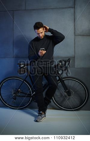 Young man using mobilephone, leaning against bicycle.