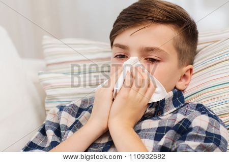 childhood, healthcare, rhinitis, people and medicine concept - ill boy with flu lying in bed and blowing his nose at home