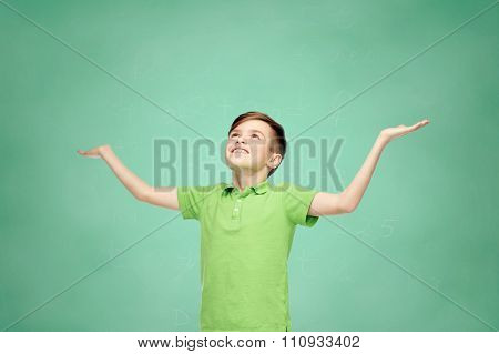 childhood, achievement, gladness and people concept - happy smiling boy in green polo t-shirt raising hands and looking up over green school chalk board background