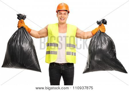 Young cheerful waste collector holding two trash bags and looking at the camera isolated on white background