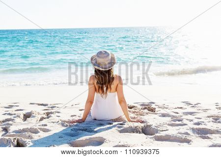 Portrait of young pretty woman with hat sitting on the beach