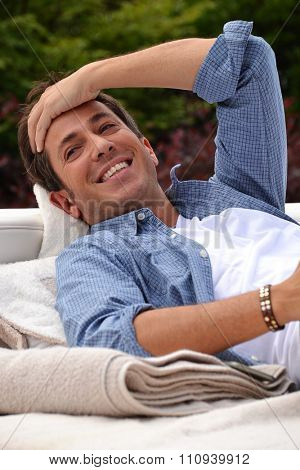 Happy Young man outdoor resort relaxing on sofa behind swimming pool and towels.