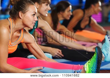 Women stretching legs in sports club