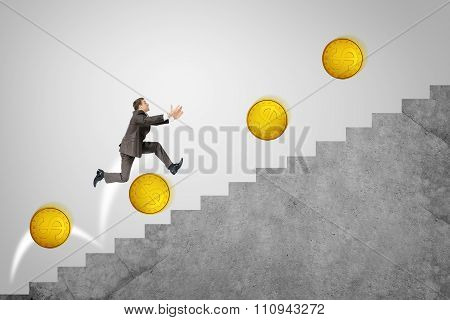 Businessman running up stairs with gold coins