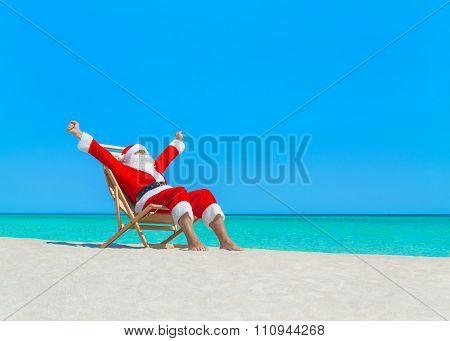 Christmas Santa Claus Enjoy Sun On Deckchair At Tropical Beach