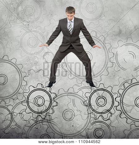 Businessman standing on cog wheels