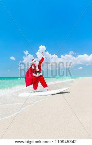 Santa Claus Windsurfer On Surfboard With Christmas Bag At Beach