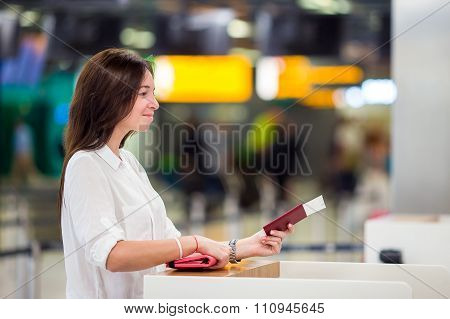 Happy woman with tickets and passports at airport waiting for boarding