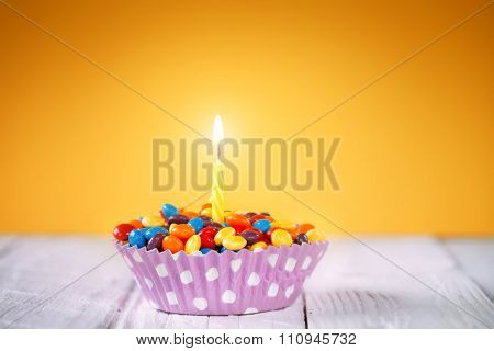 Decorated Birthday Cupcake With One Lit Candle And Colorful Cand