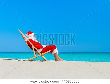 Christmas Santa Claus At Beach In Deckchair Working At Computer