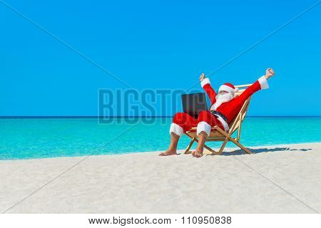 Santa Claus Hands Up At Beach In Deckchair Using Laptop