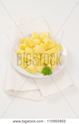 plate of raw diced potatoes on white place mat