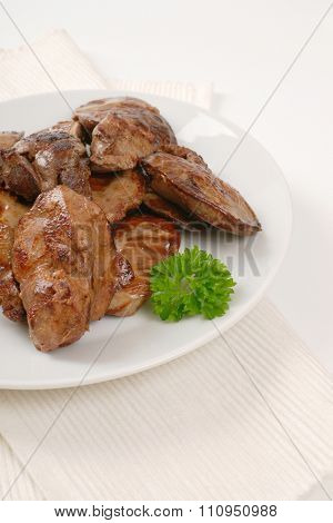 plate of pan fried chicken liver on white place mat