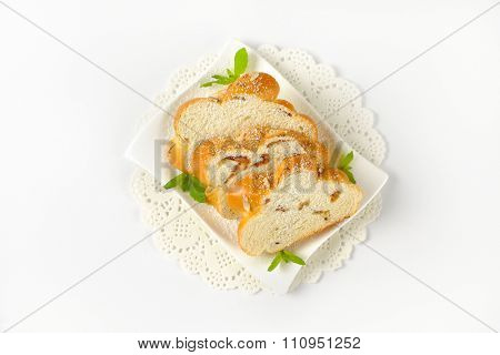 slices of sweet braided bread with almonds and raisins on white plate and lace place mat
