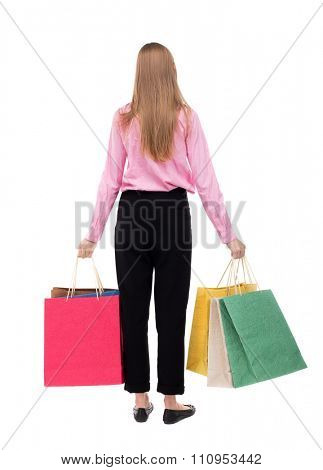 back view of woman with shopping bags . beautiful brunette girl in motion.  backside view of person. Isolated over white background. The girl in the pink shirt is held in both hands with shopping bags