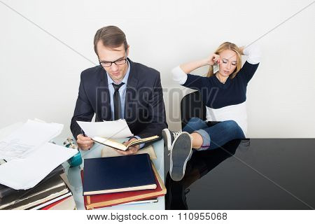woman prevents a man to work. talking phone. It distracts from business. feet on table