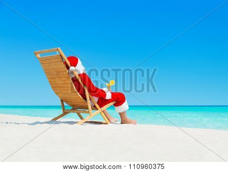 Christmas Santa Claus With Cocktail On Sunlounger At Tropical Beach