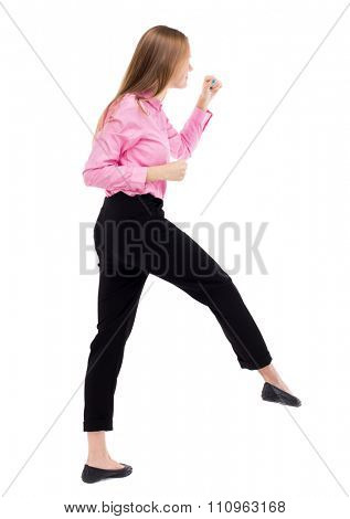 skinny woman funny fights waving his arms and legs. Isolated over white background. Woman office worker in a pink shirt has the right foot.