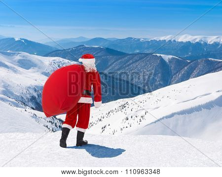 Santa Claus With Christmas Bag Against Snowy Winter Mountain Landscape