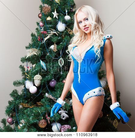 Snow Maiden sexy young woman at the Christmas tree. New year