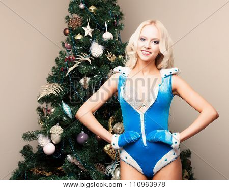 Beautiful blonde Snow Maiden sexy young woman in a blue suit and gloves at the Christmas tree. New y
