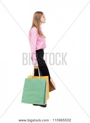 back view of going  woman  with shopping bags . beautiful girl in motion.  backside view of person. Isolated over white background. girl in the pink shirt is bent under the weight of bags.