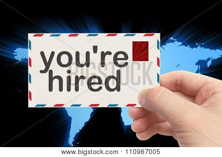 Hand Holding Envelope With You're Hired Word And World Background