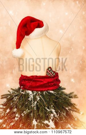 Mannequin dressed for a festive Christmas with pine branches and Santa hat