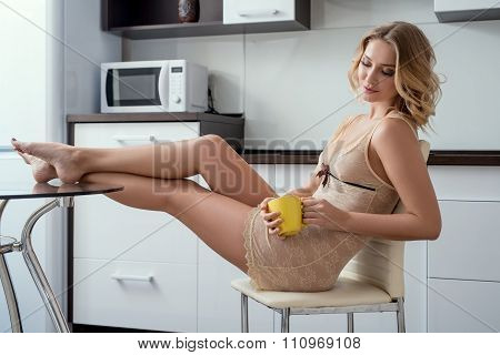 Curly blonde in negligee posing while drinking tea