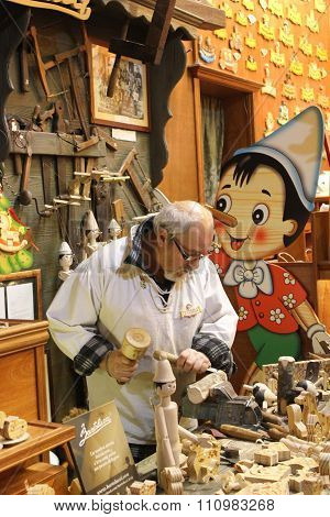 Traditional Craftsman Carving Wood In Pinocchio Shape
