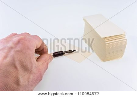 Man's Hand With An Old Pen And White Paper Cards