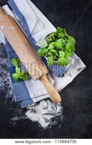 Rolling pin, vegetablers and flour on a black background.