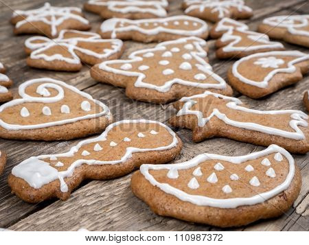 Different shape Christmas gingerbread cookies with white icing placed on wooden rustic boards