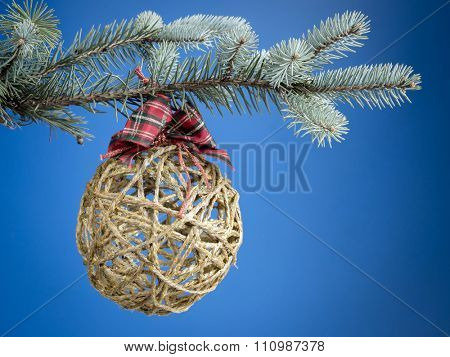 Christmas ball formed from hemp string hanging on spruce branch over blue background