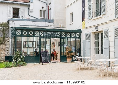 Visitors Enjoy Coffee At The Cafe Renoir In The Musee De Montmartre, Paris
