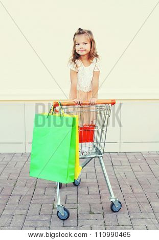 Happy Smiling Little Girl Child Sitting In Trolley Cart With Colorful Shopping Bags Having Fun