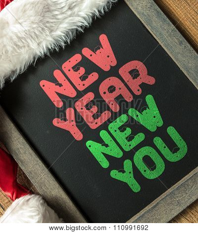 New Year New You written on blackboard with santa hat